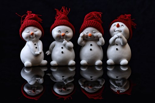 Snow people figures in different poses with stocking hats